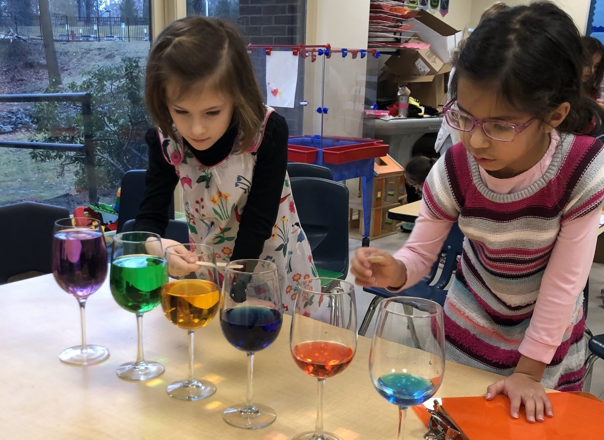 Two first grade girls work on a science project with colored water in class.
